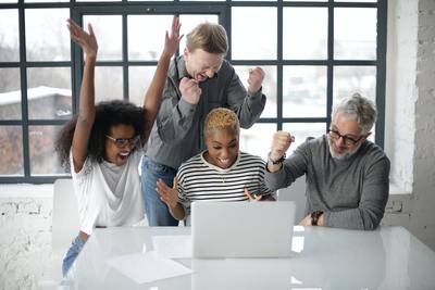 excited multiracial colleagues looking at computer screen